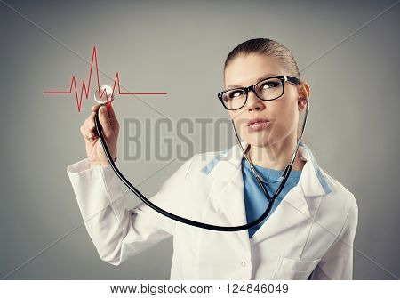 Heartbeat analysis. Conceptual shoot of young doctor cardiologist with stethoscope and heart cardiogram.