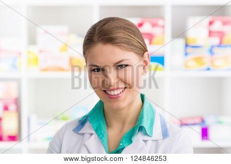 Close-up portrait of young friendly woman pharmacist standing in retail drug store selling pharmaceuticals. Healthcare and medicine.