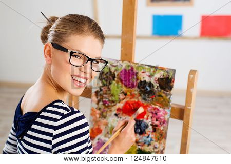 Close-up portrait of attractive cheerful female painter creating new pictorial art. Happy smiling young Caucasian woman with paintbrush standing at easel in her studio.