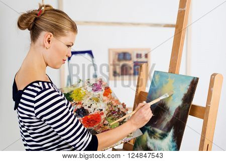 Young female paint artist working with paintbrush over picture. Attractive woman painter standing at easel with color palette.
