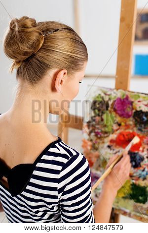 Female art student working over picture at easel in university.