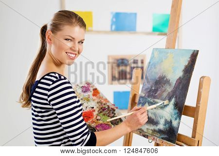 Pretty smiling woman painter drawing picture of beautiful landscape on easel. Young cheerful girl creating new artwork in studio.