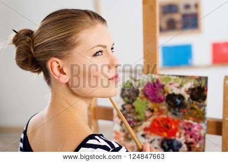Beautiful female paint artist with brush thinking to create new artwork. Young woman painter standing at wooden easel in her studio.