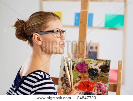 Pensive painter wearing eyeglasses with paintbrushes standing at easel in her artistic studio.