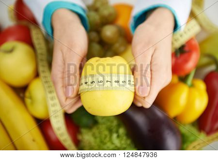 Close-up of female nutritionist hands measuring apple with tape. Woman dietitian prescribing low-calorie food to patient.