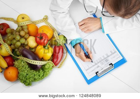 Doctor therapist writing case development form sitting at the desk in hospital. Female nutritionist prescribing diet to patient.