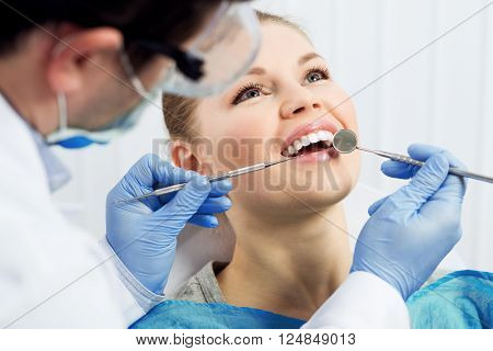 Male dentist examining patient teeth before oral operation. Young female in dental surgery office.
