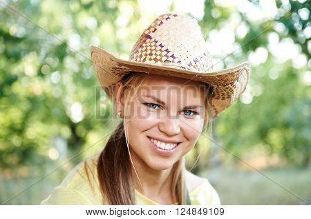 Close-up portrait of pretty smiling woman farmer wearing straw hat on nature. Female winegrower posing in the garden.