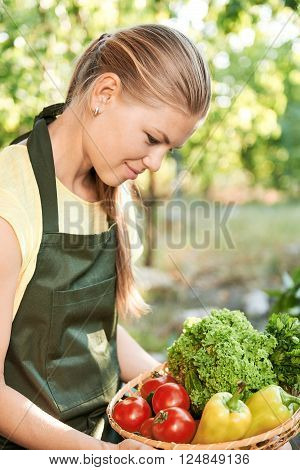 Satisfied female farmer looking at summer harvest in the yard. Attractive woman taking care of her home garden.
