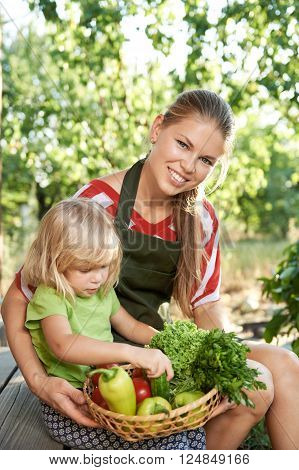 Family weekend activity in the garden. Young mother with cute daughter holding basket with vegetables and green stuff sitting on back yard.