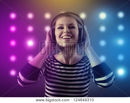 Portrait of female night club DJ enjoying disco music over colorful lights background. Young happy smiling girl clubbing in headphones.
