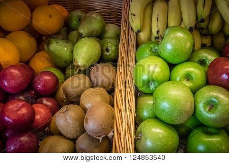 Plums, apples, pears and oranges in a bowl on a table on a self service breakfast counter in a hotel