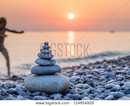 Pyramid of stones for meditation lying on sea coast at sunset. Blurred silhouette of a child coming out of the sea to the shore