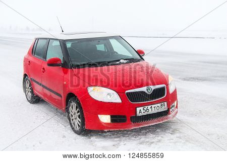 NOVYY URENGOY RUSSIA - MARCH 20 2016: Small city hatchback Skoda Fabia SE at the interurban road during the heavy snowstorm.