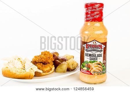 LLANO TX - APR 6 2016: Bottle of Louisiana Fish Fry Products Remoulade Sauce with Shrimp Po Boy Sandwich on white background with copy space.