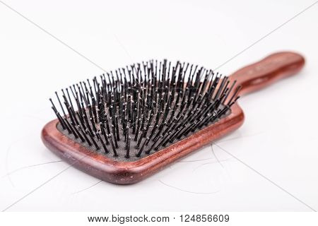 Comb with strand of hair sticking on it against white background