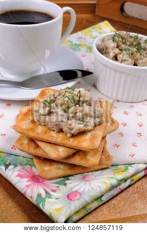 Appetizer of fish paste (forshmak) on a cracker with a cup of coffee