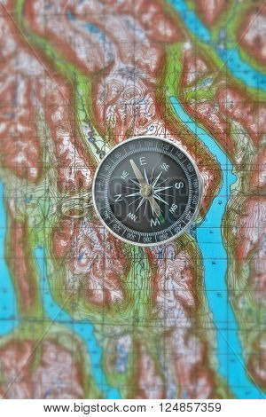 Magnetic compass is located on a topographic map. Orienteering in the wilderness