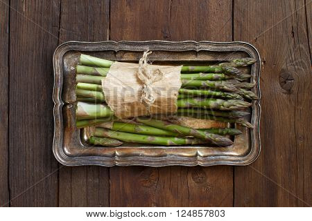 Bundle of fresh asparagus spears on a metal tray