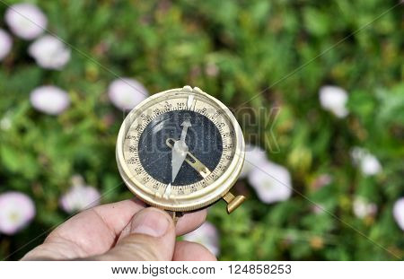 The compass in his hand. Magnetic compass in hand on the green meadows.