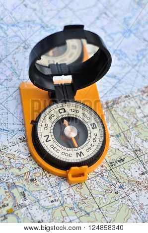 Compass on the map. Magnetic compass in the expanded form is situated on a topographic map.