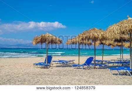 Chrisi (Chrysi) island beach background with straw sunshades, Crete, Greece. One of the most beautiful uninhabited island of Greece.