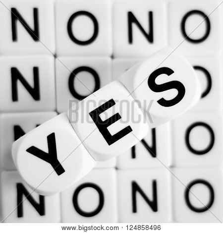 Word yes in black letters on white cubes, with word no repeated underneath in black letters on white tiles