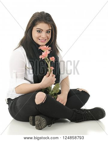 A pretty teen girl happily holding a small bouquet of pink flowers while sitting on the floor in a black and white outfit.  On a white background.
