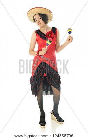 An attractive teen girl dancing with maracas in her red and black Mexican dress and straw sombrero.  On a white background.