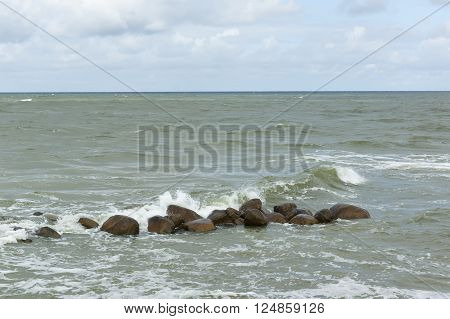 stones lie in a raging sea under blows of big waves
