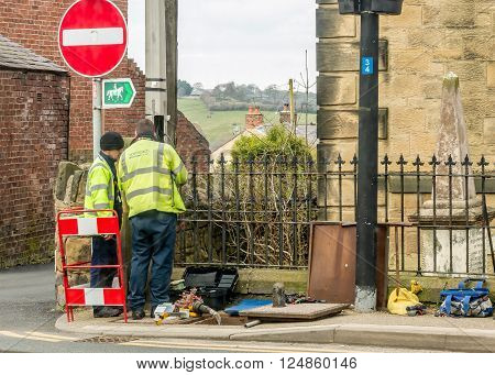 WREXHAM WALES UNITED KINGDOM - MARCH 21 2016: Openreach workers fixing BT (British Telecom) telephone line outside in the street.