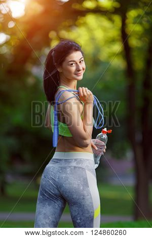 The back of muscular young woman athlete with a skipping rope drinking water