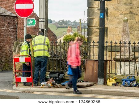 WREXHAM, WALES, UNITED KINGDOM - MARCH 21, 2016: Openreach workers fixing BT (British Telecom) telephone line outside in the street, and a passer by.