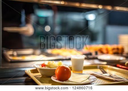 Tray with a breakfast being collected from a breqakfast counter in a restaurant in a hotel
