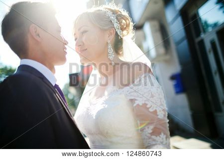 Wedding couple looking to each other, lens flare effect, outdoors