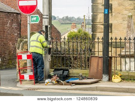WREXHAM WALES UNITED KINGDOM - MARCH 21 2016: Openreach workeman fixing BT (British Telecom) telephone line outside in the street.