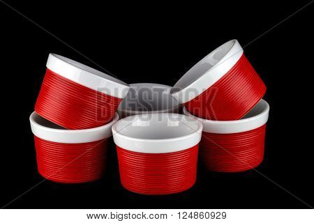 Red and white ramekin dishes stacked against a black background