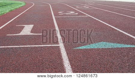 Lanes on a running track just before the bend,  with emphasis on lane one.