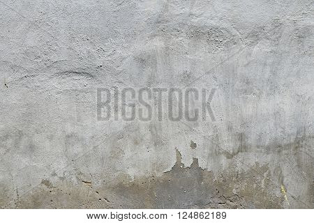 Old white and grey painted lime plaster concrete wall with weatherstains runs and defects