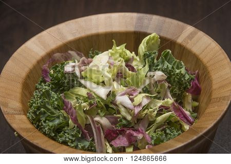 Colorful kale salad in a wooden bowl