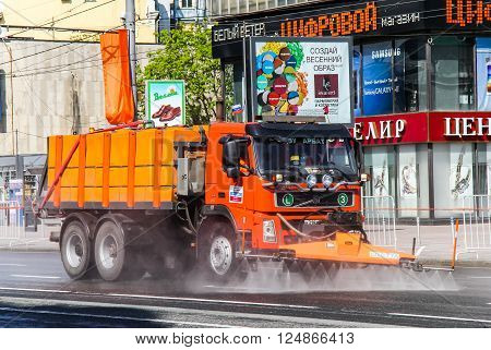 MOSCOW, RUSSIA - MAY 6, 2012: Red watering and cleaning machine Volvo FM12 in the city street.