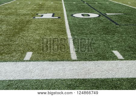 The ten yard line on a turf football field from the sideline.