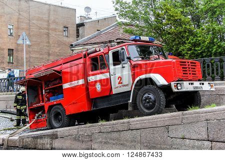 SAINT PETERSBURG RUSSIA - MAY 25 2013: Fire engine ZIL 433112 getting water from the canal.