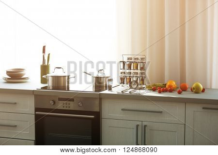 Modern kitchen interior with white furniture and electric stove beside the window