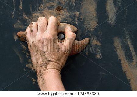 Mud race runners,hand grasping onto a wall climbing handhold