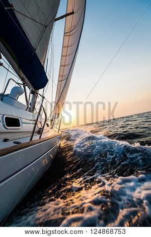 Yacht sailing in open sea at sunset