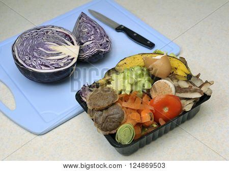 Kitchen raw food waste beside cabbage being prepared collected in a reused container for adding to a home composter or compost heap.