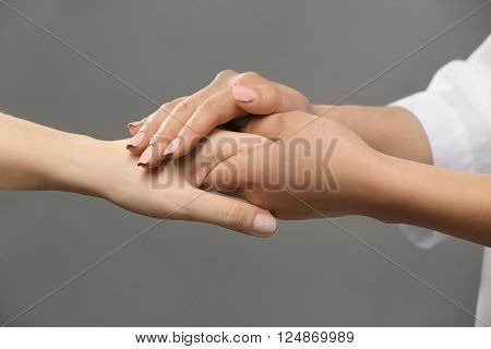 Young female doctor holding patient's hand on grey background
