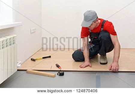 Man installing new laminated wooden floor in the room