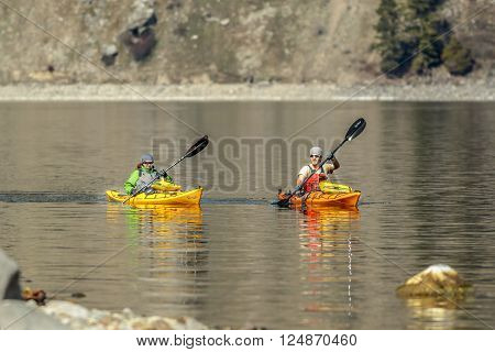 Bayview, Idaho USA - 03-31-2016. An editorial image of two kayakers paddling on Lake Pend Oreille in Idaho.